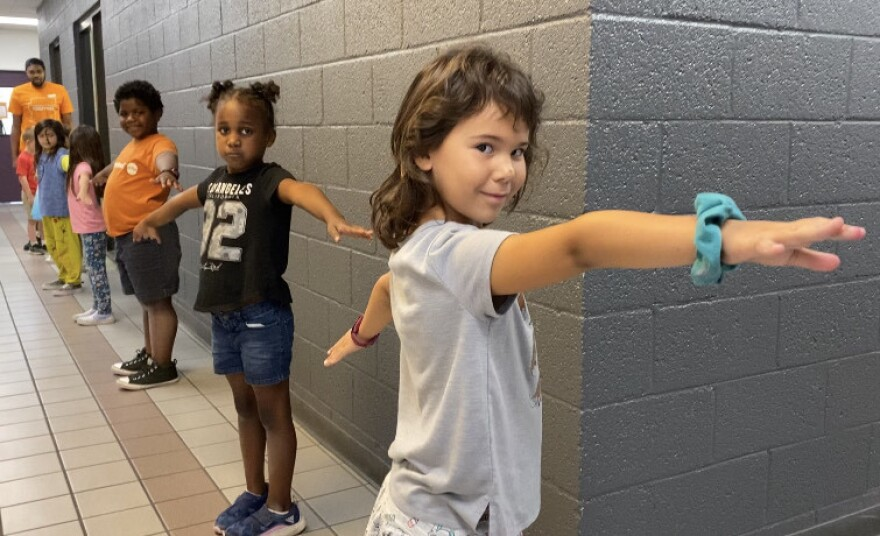 "To help with social distancing, children at Valley of the Sun YMCA sites in Arizona were taught to make ""airplane arms"" when standing in line."