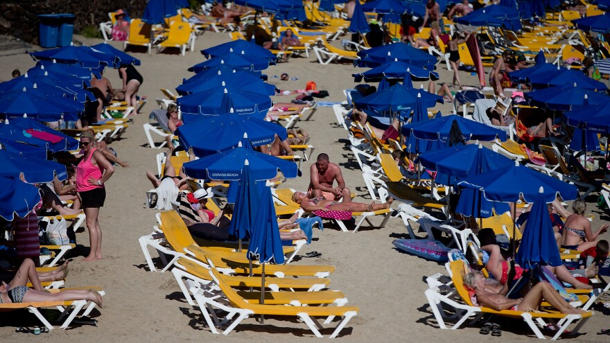 Tourists lay on rows of sun umbrellas on Playa Blaca beach on April 13 in Lanzarote, Spain. Oil exploration began recently in the waters off the coast of the popular tourist destination, despite the opposition of the local residents and government, and environmental organizations.
