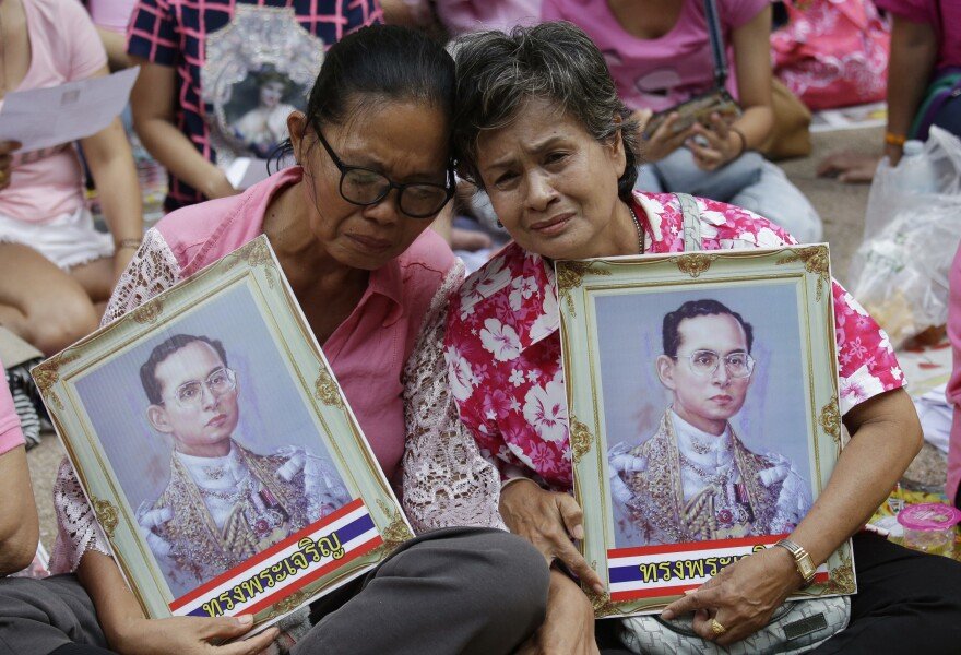 Two women cry as they pray for Thailand's King Bhumibol Adulyadej outside Siriraj Hospital in Bangkok on Thursday. The king's death was announced shortly afterward. The world's longest reigning monarch, the king was on the throne for 70 years.