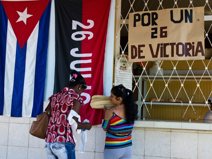 The flag of the July 26 Movement hangs to the right of the Cuban flag, behind two women buying bread in the city of Artemisa.