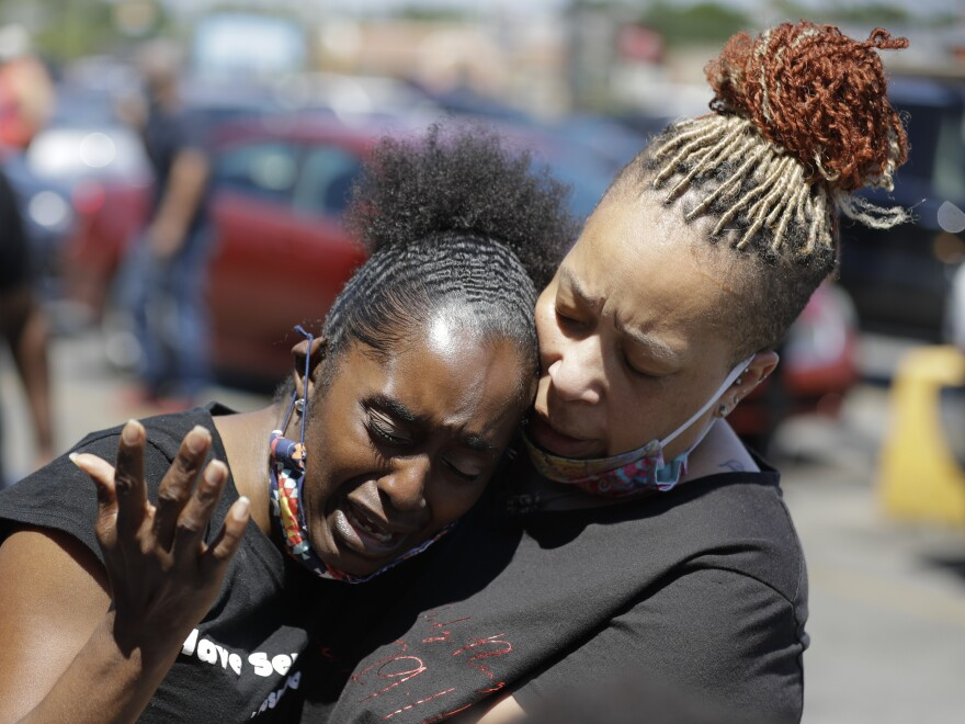 Two women pray in Louisville, Ky., in early June near the intersection where David McAtee was killed. Louisville police say video obtained from security cameras at McAtee's barbecue restaurant and an adjoining business show that McAtee fired a gun as police and National Guard soldiers were enforcing a curfew approached his business.