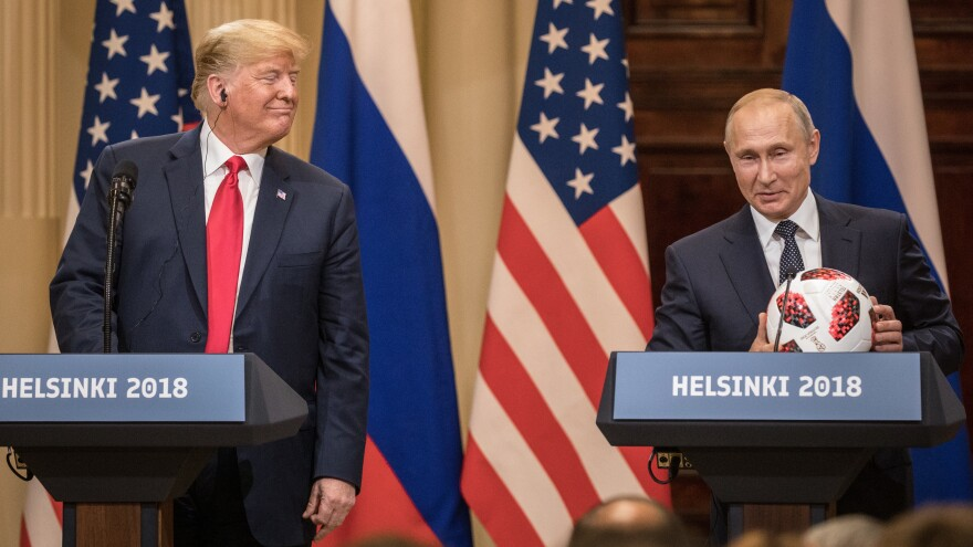 Russian President Vladimir Putin offers a World Cup football to President Trump during a joint news conference after their summit on July 16, 2018, in Helsinki.