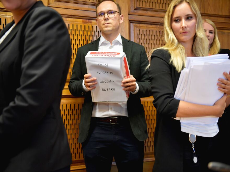 Court staff hand out the verdict to the press at the end of a hearing in US rapper A$AP Rocky's assault trial, in Stockholm, Sweden.