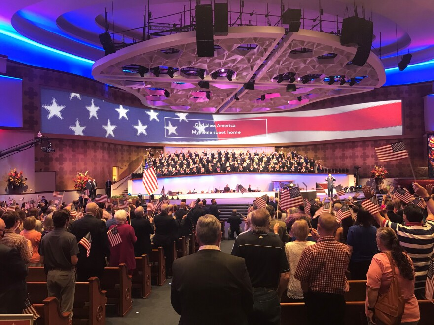 Worshippers wave American flags at Celebrate Freedom Sunday at First Baptist Dallas on June 28, 2020.