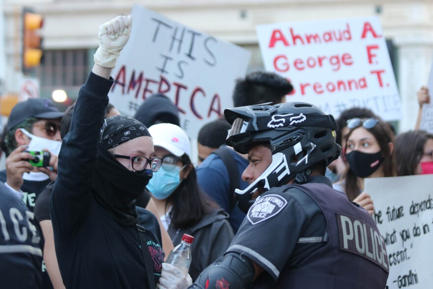 A protestor wears a mask and gloves during the COVID-19 pandemic in San Antonio.