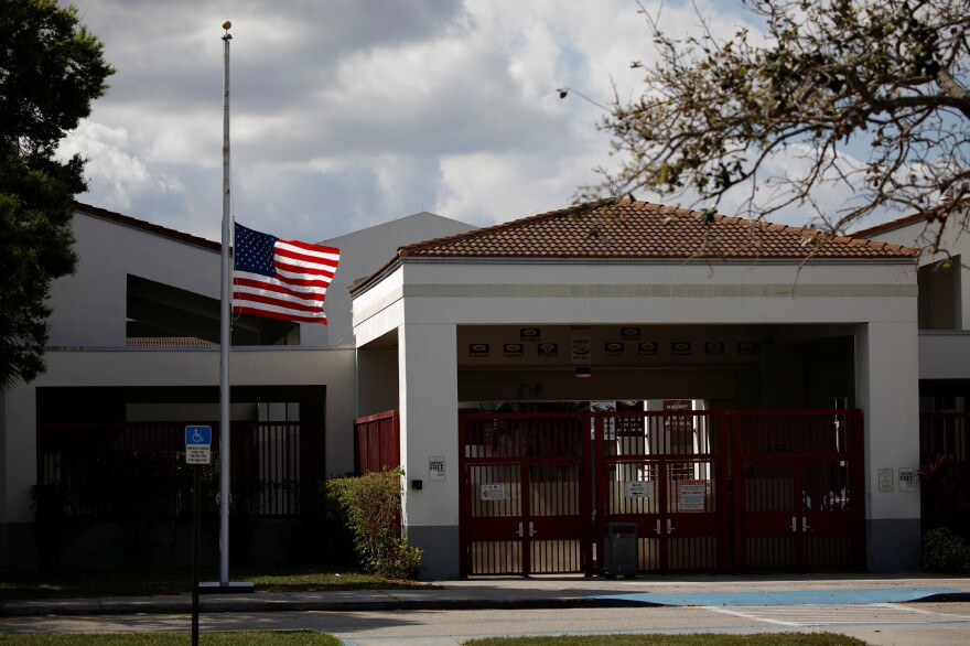 A flag flies at half mast at the entrance to Marjory Stoneman Douglas High School, following a mass shooting at the in Parkland, Fla., school earlier this month.