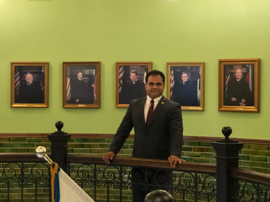 K.P. George, pictured in the historic Fort Bend County Courthouse in Richmond, Texas, stands before the photos of all the previous County Judges who preceded him in the office. The Indian immigrant is the first minority ever elected to the seat.