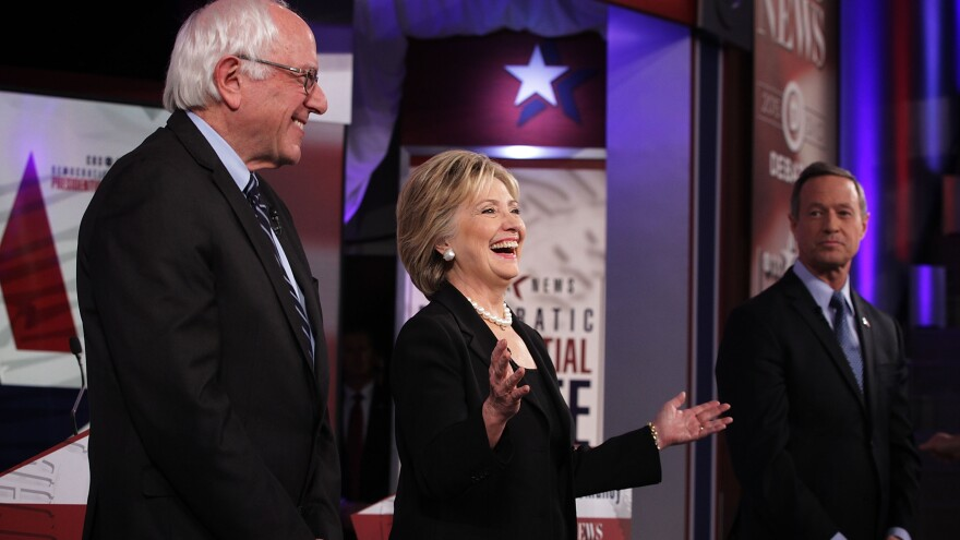 Democratic presidential candidates Bernie Sanders, Hillary Clinton and Martin O'Malley stand on the stage prior to Saturday's Democratic primary presidential debate in Des Moines, Iowa.