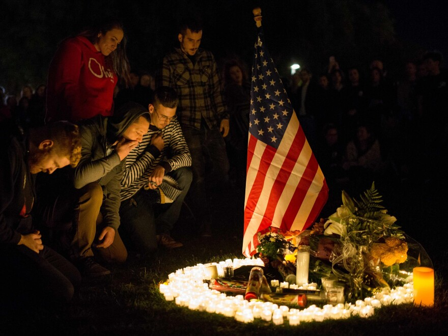 Friends and family members pay tribute to victims of the Borderline Bar & Grill shooting in Thousand Oaks, Calif. A vigil drew thousands of people on Thursday as the community coped with the loss of 12 victims. The gunman also died.