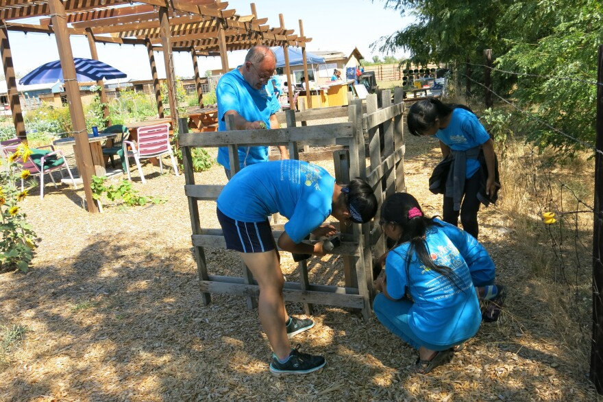 Kids in the program construct a compost bin under the supervision of Chris Lines, whose wife, Denise, founded Growing Colorado Kids.