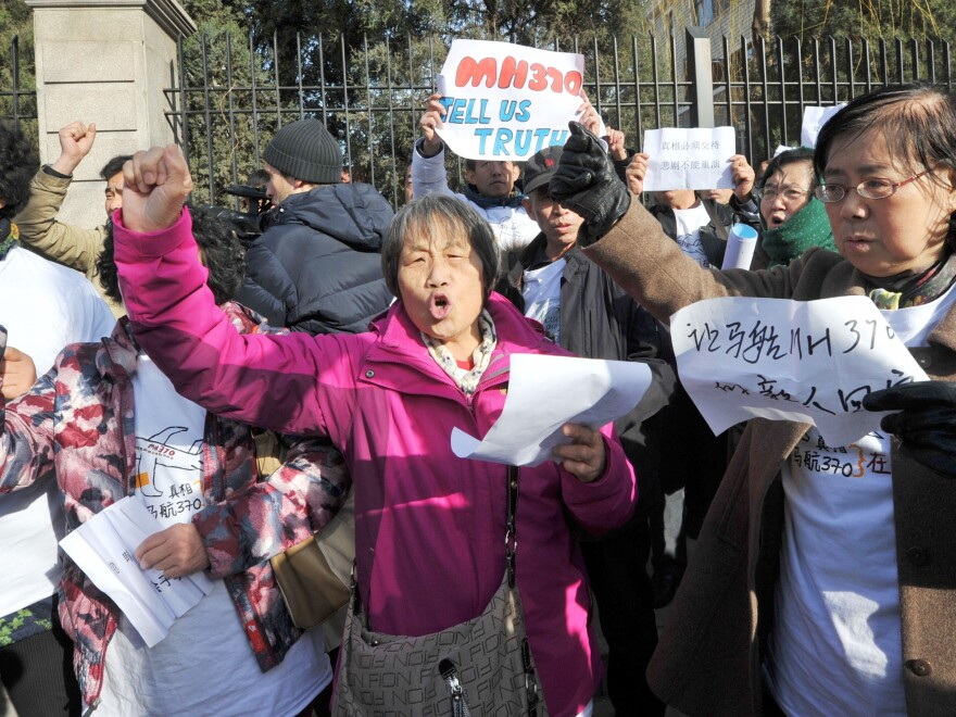 About 30 people believed to be relatives of Chinese passengers of Malaysia Airlines Flight MH370 that went missing a year ago, protest near the Malaysian Embassy in Beijing on Sunday.