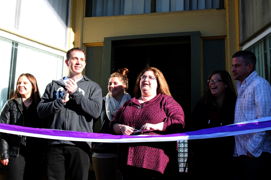 Karie Pennington (left), Robert Riley, Mary Maybery-Daniels (center) and Chad Sabora (right) gather for the ribbon-cutting ceremony outside their nonprofit's outreach center in St. Louis' Dutchtown neighborhood Fri. Dec. 18, 2015.