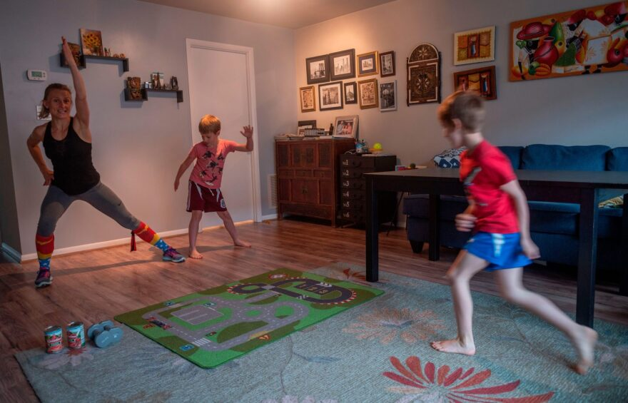 Mimicked by her son Daniel (C), Paulina Mansz, a group fitness instructor, records a workout session for her clients while her other son Javier plays, as she continues to instruct from home in Arlington, Virginia.