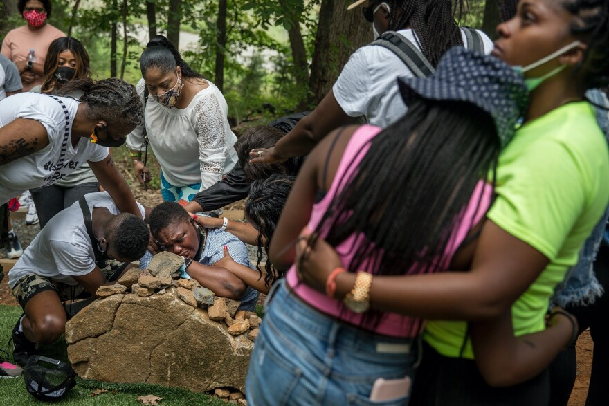 Surrounded by loved ones, Pastor Michelle Thomas grieves at the stone marking her son's grave at the African American Burial Ground for the Enslaved at Belmont. Her son, Fitz Alexander Campbell Thomas, 16, died in June and is the first free African American to be buried at the site.