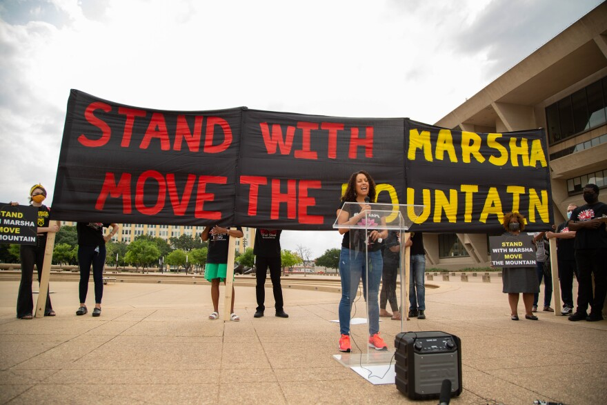 "Environmental activists stand behind a podium in front of Dallas City Hall and hold a sign that reads, ""Stand With Marsha Move The Mountain"" in yellow and red paint."