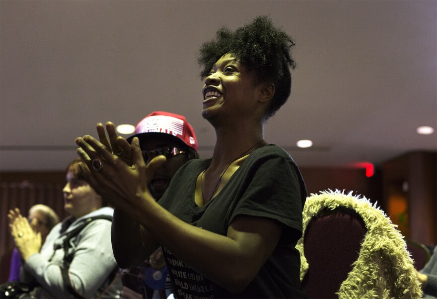 Ferguson resident Laura Charles applauds for a speaker during the public comment portion of Saturday's meeting.