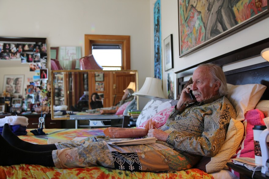Photo of a man lying on a bed wearing brightly patterned clothes.