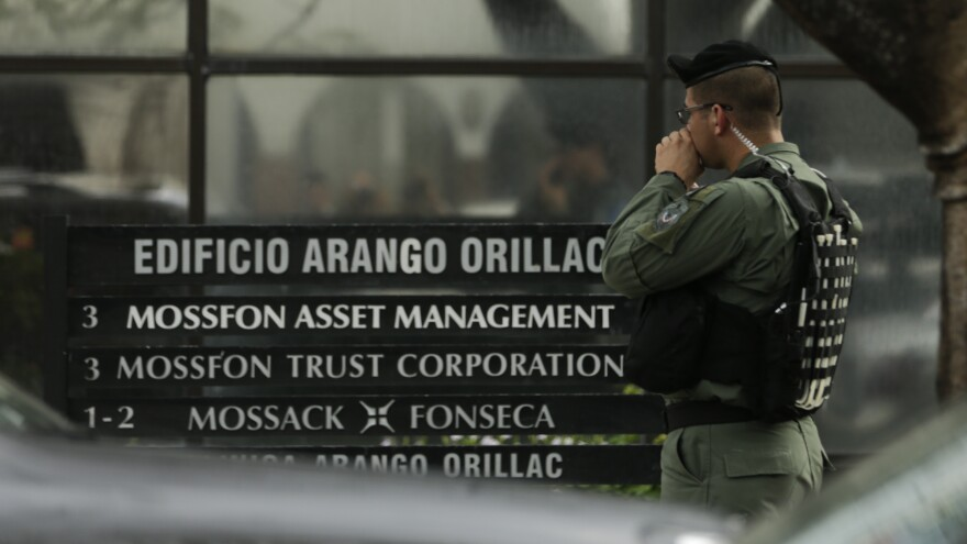 A police officer stands outside the Mossack Fonseca law firm Tuesday as organized crime prosecutors raid the offices in Panama City.