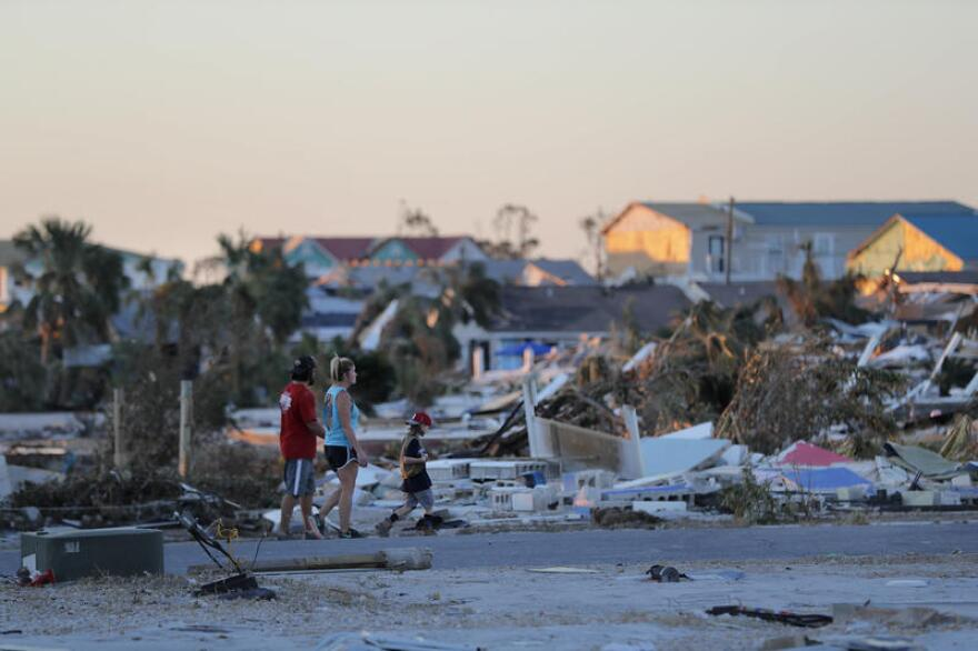 People walk amidst rubble in the aftermath of Hurricane Michael in Mexico Beach, Fla., Saturday, Oct. 13, 2018.
