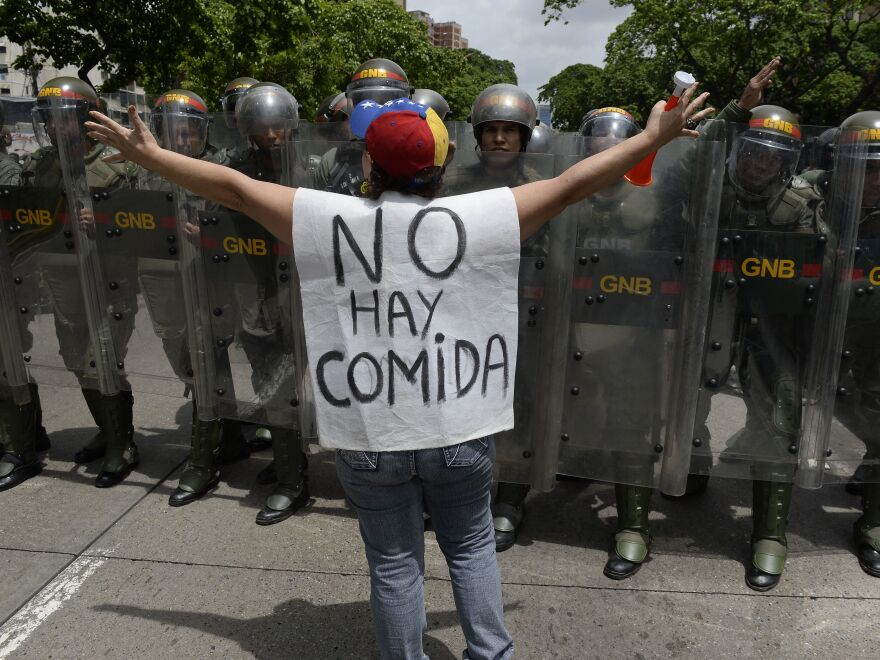 "A woman with a sign reading ""There is no food"" protests against new emergency powers decreed this week by President Nicolas Maduro in front of a line of policemen in Caracas on May 18, 2016. / AFP / FEDERICO PARRA (Photo credit should read FEDERICO PARRA/AFP/Getty Images)"