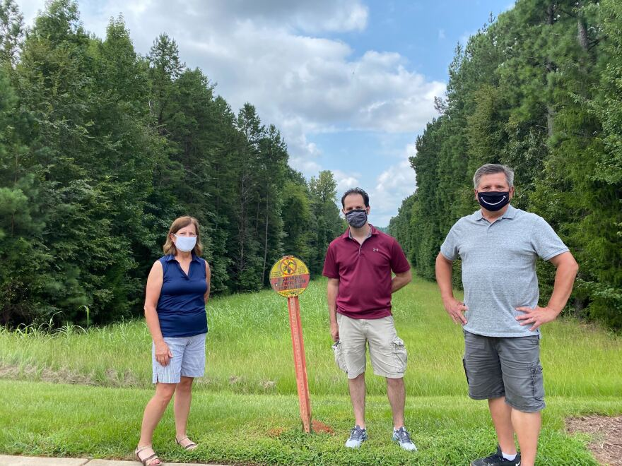 Pavilion Estates residents Catherine Graffey, Jake Cohen, and Rick Lyke stand near the pipeline's right of way, marked by signs.