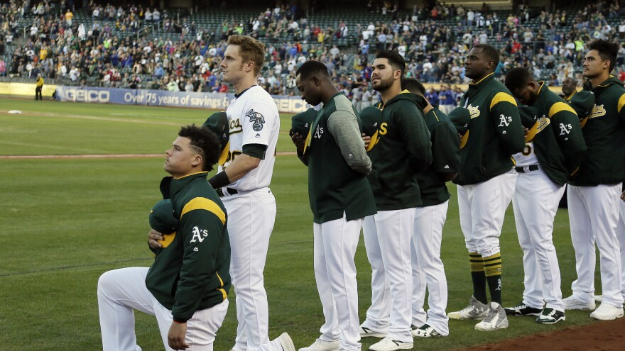 Oakland Athletics catcher Bruce Maxwell kneels during the national anthem Saturday in Oakland. Maxwell is the first Major League Baseball player to kneel during the national anthem.
