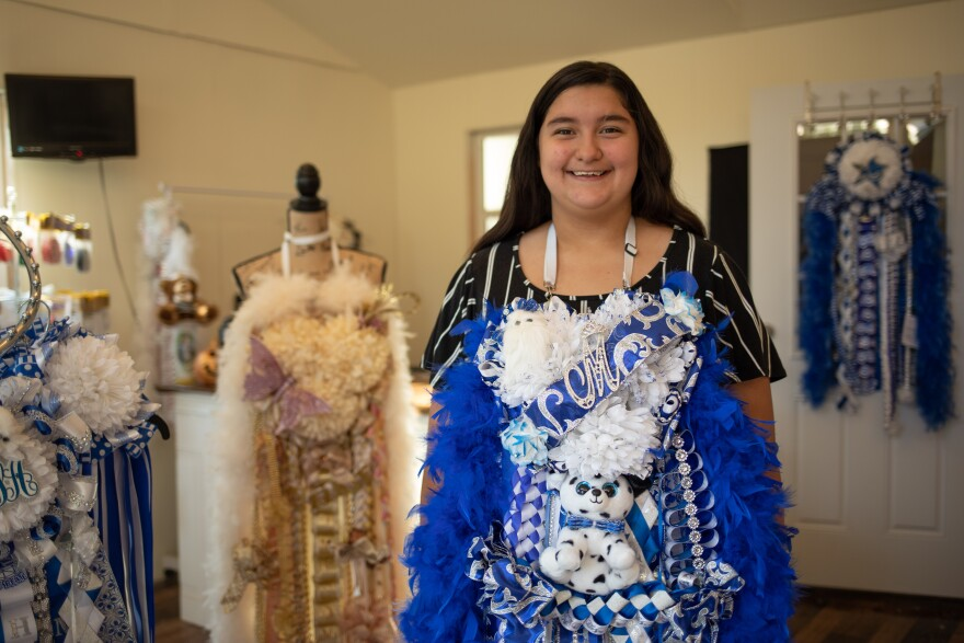A girl smiles, wearing an elaborate blue mum around her neck.