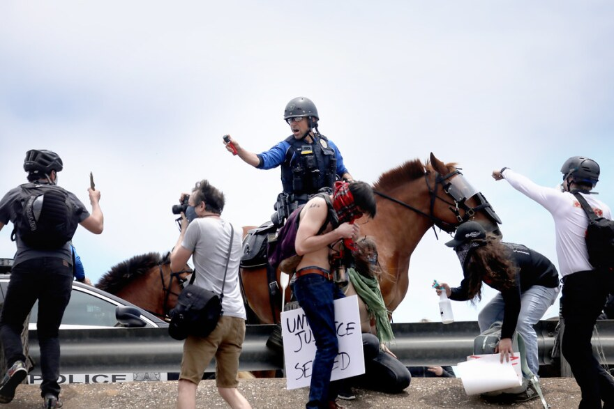 Mounted police officers use pepper spray on protesters attempting to get on Interstate 35 Saturday afternoon.