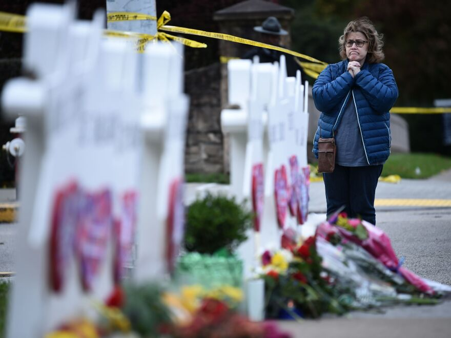 A woman prays before a memorial outside the Tree of Life synagogue after a shooting there left 11 people dead in Pittsburgh on Saturday.