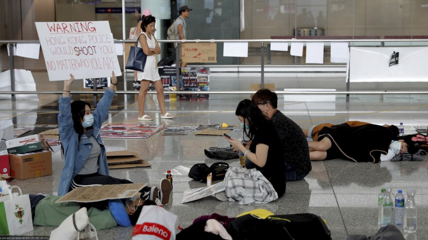 A protester shows a placard to travelers at Hong Kong International Airport on Wednesday. Flight operations resumed at the airport Wednesday morning after two days of disruptions.