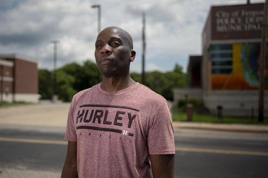 "Citizen journalist Tony Rice, who goes by ""@search4swag"" on Twitter, stands in front of the Ferguson Police Department, where he gained a reputation in 2014 for consistent protest coverage. Since George Floyd's death, he has covered nearly every demonstration in the St. Louis region."