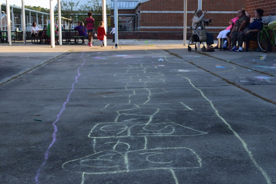 A hopscotch game is drawn in chalk. Children play while adults talk.