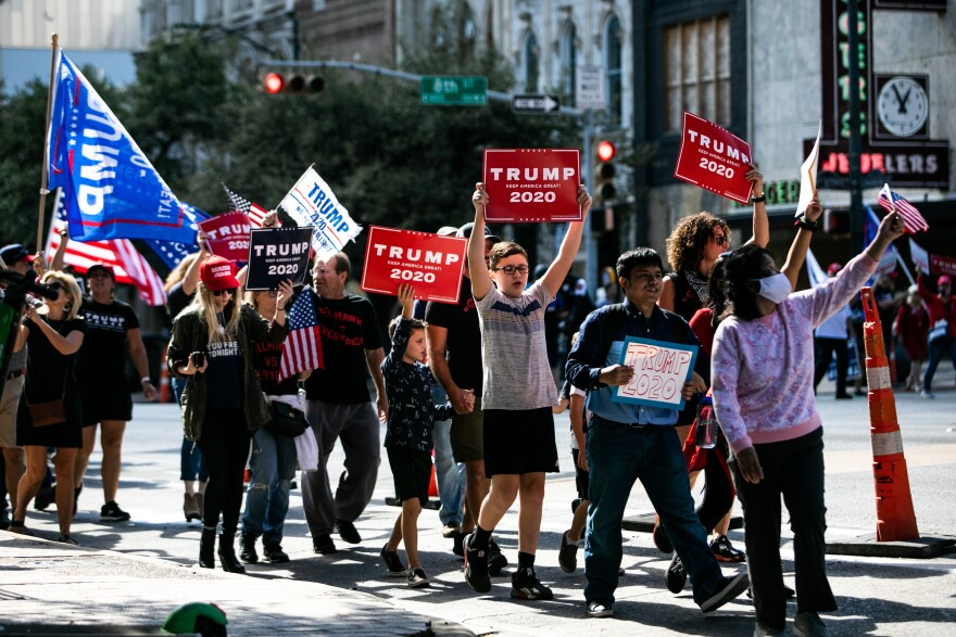 Supporters of President Donald Trump march on Congress Avenue.