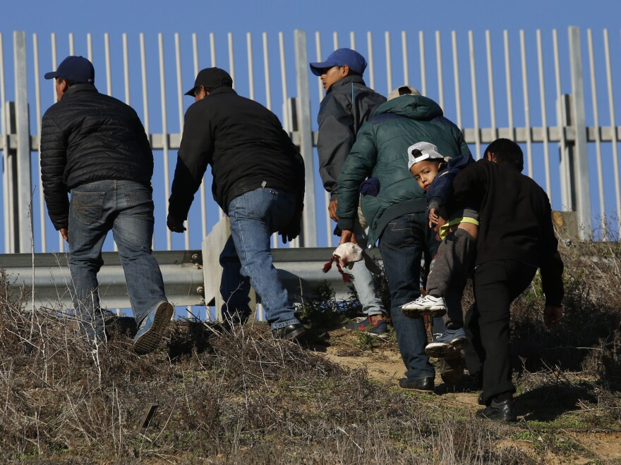 Migrants, one carrying a child, who plan to turn themselves over to U.S. border agents, walk up the embankment after climbing over a U.S. border wall from Playas de Tijuana, Mexico, last week. On Tuesday, members of the Hispanic Caucus called for improved medical facilities and trained personnel at ports of entry.