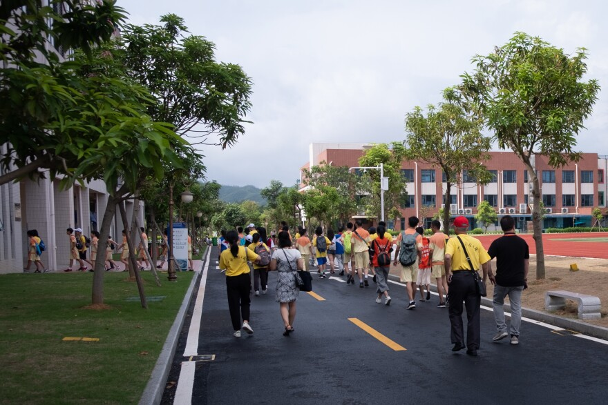Students make their way down the road near athletic fields at the Biguiyuan private school in Taishan City.
