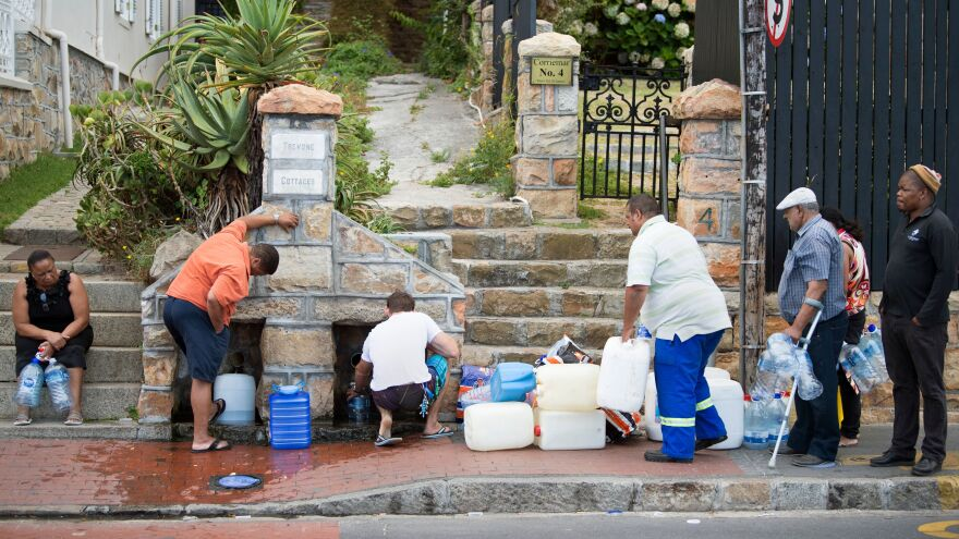 People collect drinking water from pipes fed by an underground spring last week in Cape Town. Next month, the city will slash its individual daily water consumption limit to 13.2 gallons, the mayor said, as the city battles its worst drought in a century.