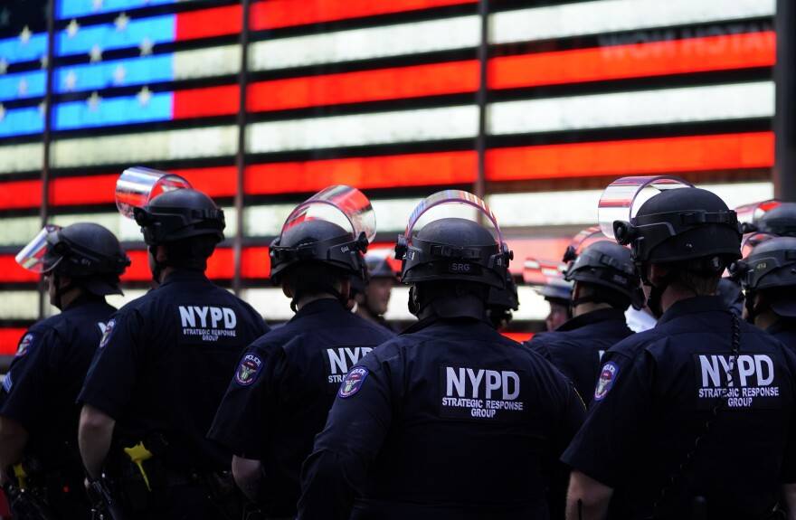 New York City police officers watch demonstrators in Times Square on June 1 during a Black Lives Matter protest.
