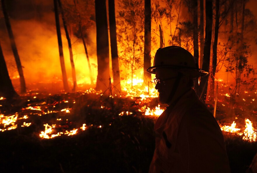 Crews monitor fires and begin back burns between the towns of Orbost and Lakes Entrance in East Gippsland, east of Melbourne, on Thursday.