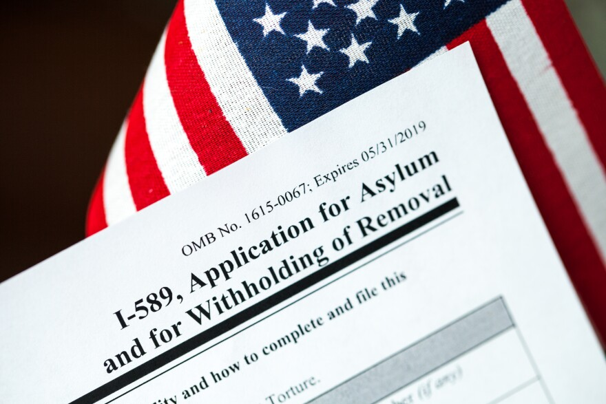 Photo of an asylum application in front of an American flag.
