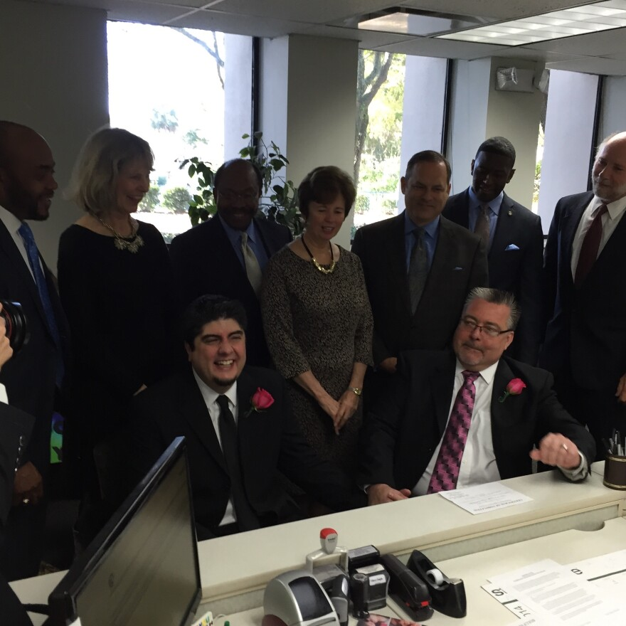 Myles Robertson and Jim Van Riper (seated, L-R) flanked by city and county officials as they register for their marriage license.