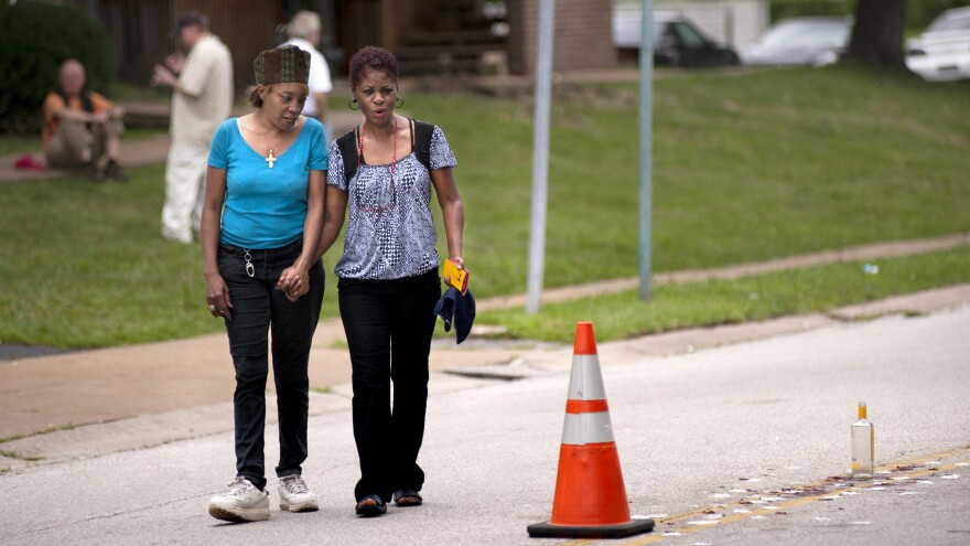 Tammy Miles (left) and Janice Battle look at the scene where Michael Brown, 18, was shot in Ferguson, Mo., over the weekend.