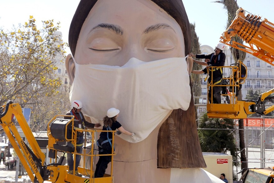 Several South Florida local governments have issued orders that urge or require people to wear masks inside essential businesses. Here, workers in Spain place a medical mask on a figure that was to be part of a Valencia festival that was canceled.