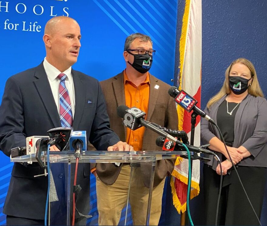 Man speaks at podium with man and woman standing behind him with masks