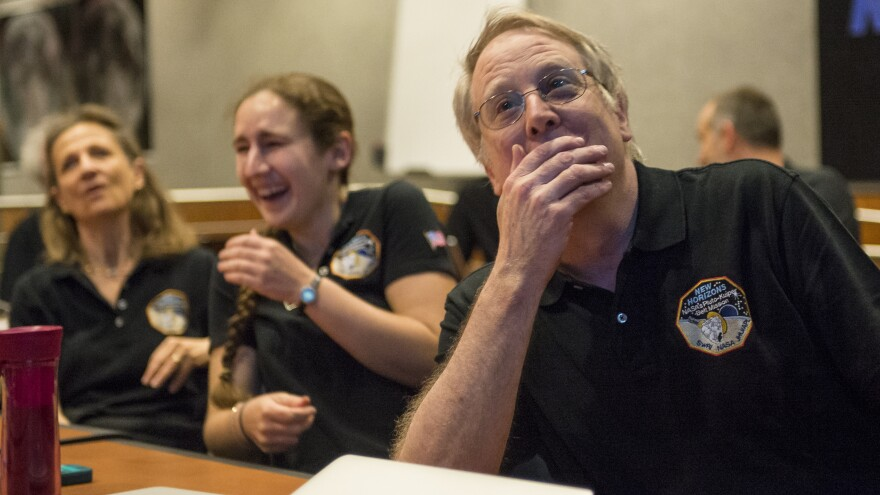 Members of the New Horizons science team react to seeing the spacecraft's sharpest image of Pluto before making its closest approach Tuesday. They monitored the Pluto mission from the Johns Hopkins University Applied Physics Laboratory in Laurel, Md.