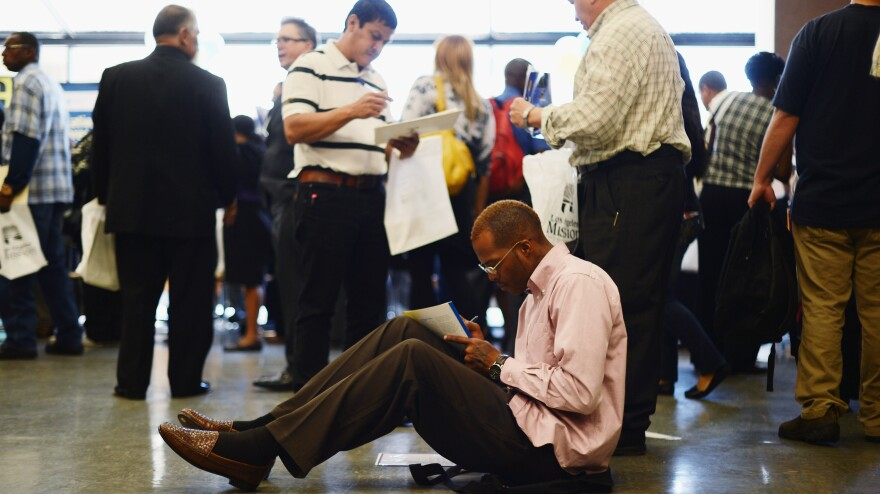 Aaron Moore completes a job application at a Los Angeles career fair on Thursday. Job growth has slowed sharply since the winter, the government said Friday.