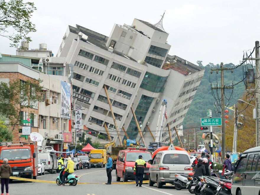 Rescue and emergency workers block off a street where a building came off its foundation, the morning after a 6.4 magnitude quake hit the eastern Taiwanese city of Hualien, on Wednesday.