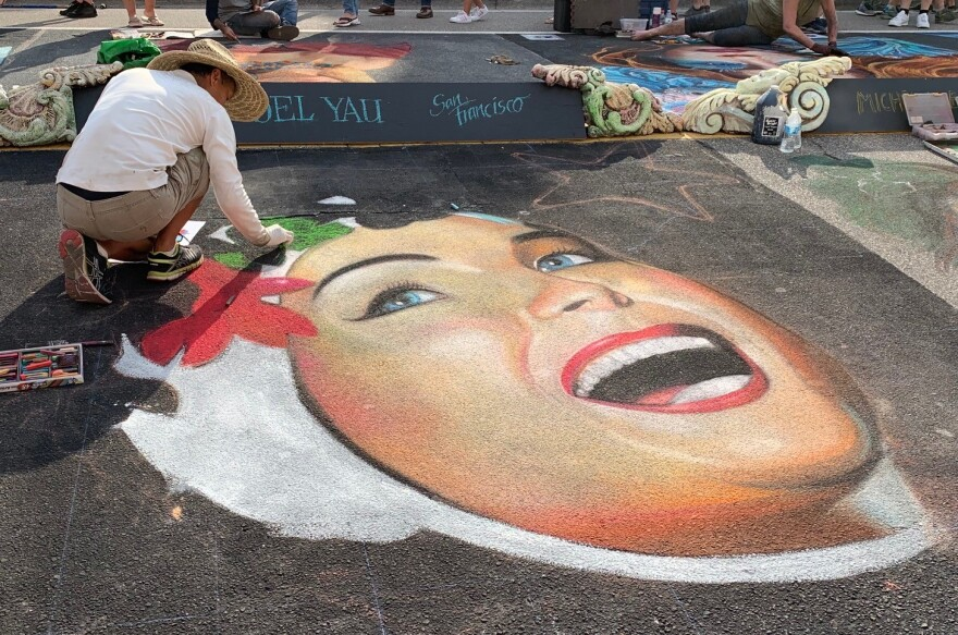 A chalk artists draws a woman;s face on the ground