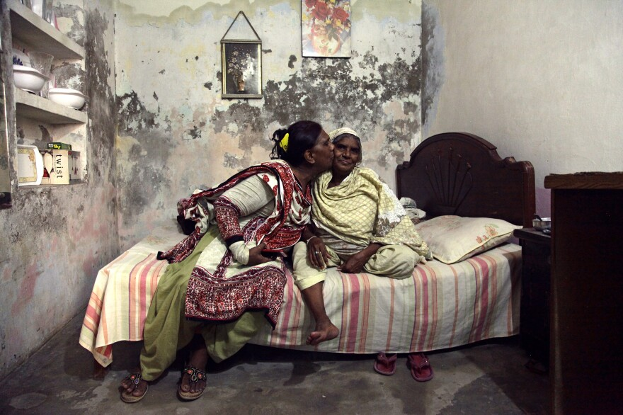 Ashi kisses her mother in the small basement apartment they share in Lahore.
