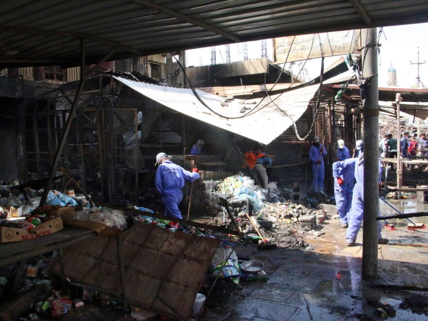 Iraqi workers clean the site of a truck bomb attack that hit the area a day earlier at Khan bani Saad town, eastern Baghdad, Iraq, on Saturday. At least 115 people were killed in what's described as the single deadliest such attack in the country in a decade.