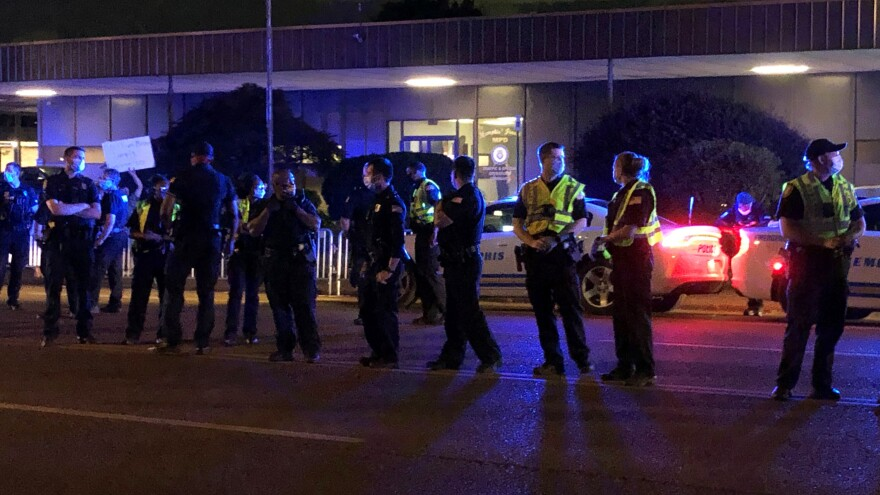 Officers form a line in front of a police precinct May 27, during a protest over the death of George Floyd.